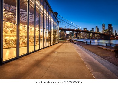 New York City, NY, USA - August 27, 2018: Brooklyn Bridge Park with Jane's Carousel at twilight with view on the skyscrapers of Lower Manhattan and the Brooklyn Bridge