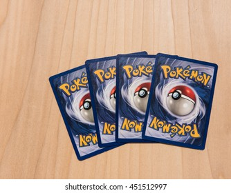 New York City, NY, USA -  July 12, 2016: Four Pokemon trading cards in a row on a wooden surface.  Illustrative Editorial
