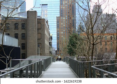 New York City, NYC / United States of America - January 2020: the view on the vintage railroad reconstructed into urban park High Line. A group of people walks on wooden sidewalk from far.