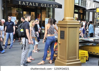 New York City, NY/United States-05/18/2015: An attractive young woman in tight jeans talks with friends near the Flatiron district.
