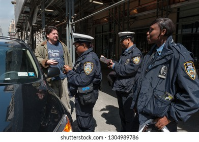 New York City, NY/USA- May 6, 2009: Man wearing Galveston, TX t-shirt looks on in disbelief as city parking agents issue him a parking fine for having an expired meter.