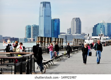 NEW YORK CITY - OCT 09 2010:Visitors looks at Jersey City from Battery Park. It's an important transportation terminus, distribution and manufacturing center for the Port of New York and New Jersey.