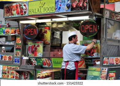 NEW YORK CITY - OCT 09 2009:Worker in Arabic fast food stand sale Halal food in Manhattan New York City.Halal  is foods that Muslims are allowed to eat under Islamic dietary Islamic Sharia law.