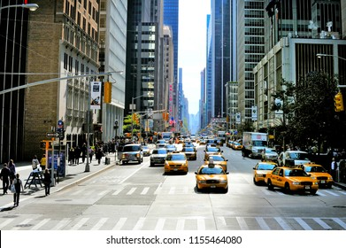 NEW YORK CITY - OCT 10 2009: New York yellow taxi cabs rush through Sixth Avenue in the Midtown Manhattan of New York City.