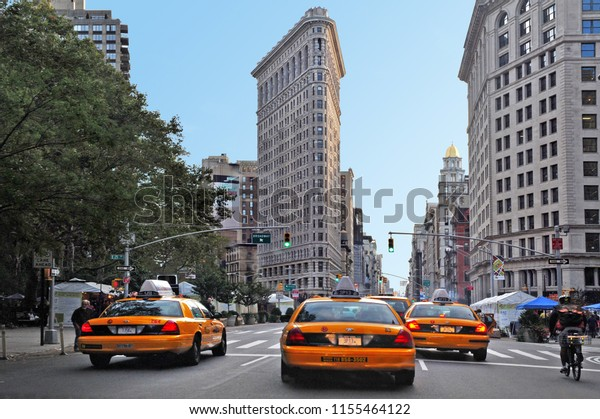 NEW YORK CITY - OCT 10 2009: New York yellow taxi cabs rush through Fifth Avenue under the Flatiron Building in the Midtown Manhattan of New York City.
