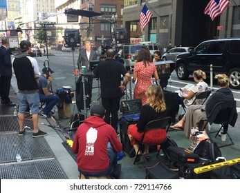 NEW YORK CITY - OCT 2017: A video production crew films videos a news reporter near Times Square. Cameras, lights, teleprompter, producer, director, talent, audio.