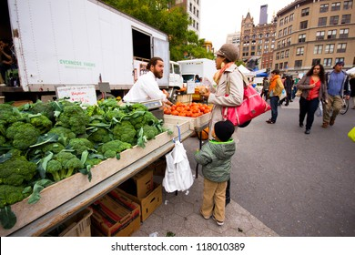 NEW YORK CITY - OCT 26:  Woman selects produce at Union Square Greenmarket in NYC on Oct. 26, 2012. This famous farmers' market began in 1976 and has grown to 140 farmers during peak season.