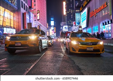 NEW YORK CITY - OCTOBER 06, 2016: Two yellow cabs driving on 7th Avenue at night time with Times Square in the background