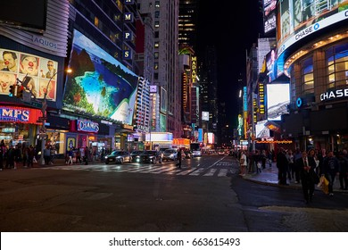 NEW YORK CITY - OCTOBER 07, 2016: Neon light from stores and billboard signs reflecting in the asphalt of 7th Avenue, at night time