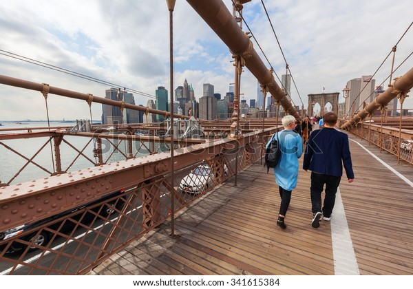 NEW YORK CITY - OCTOBER 08, 2015: Brooklyn Bridge with unidentified people in NYC. Its one of the oldest bridges of either type in the US and an icon of NYC as well as a National Historic Landmark