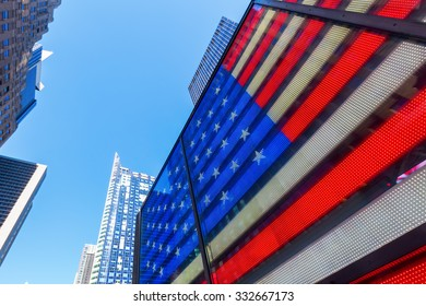 NEW YORK CITY - OCTOBER 10, 2015: neon US flag at Times Square. Times Square is one of the worlds busiest pedestrian intersections and a major center of worlds entertainment industry