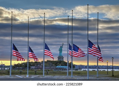 NEW YORK CITY - SEPTEMBER 11: Statue of Liberty seen behind US flags at half staff on the morning of September 11, 2014 in New York City.