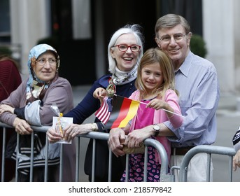 NEW YORK CITY - SEPTEMBER 20 2014: the 57th annual Steuben Parade on Fifth Avenue celebrates German-American heritage prior to Central Park's Oktoberfest. Family watching parade with US & German flags