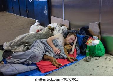 NEW YORK CITY - SEPTEMBER 20 2016: Homeless couple sleep as man cuddles with dog under blanket on sidewalk in downtown Brooklyn