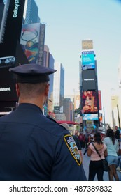 New York City - September 2016: NYPD police officer stands proud in Times Square Manhattan patrol tourists enjoying the landmark to ensure safety and protect public from criminal activity and threats.