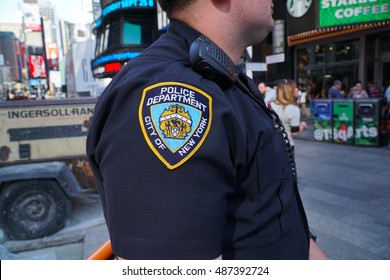 New York City - September 2016: NYPD officer stands guard in Times Square Manhattan patrol and survey public tourists looking for suspicious activity and safety threats. Police Department patch sleeve