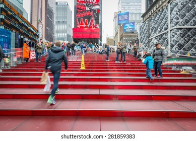 NEW YORK CITY - SEPTEMBER 23: Tourists on the red stairs of Duffy Square, September 23, 2014 in New York City. The recent transformation of the square allows for increased pedestrian traffic.