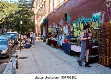 NEW YORK CITY - SEPTEMBER 24, 2016:  Woman in red dress trying sunglasses at a street flea market in East Village on Manhattan