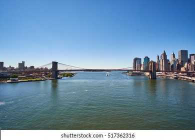 NEW YORK CITY - SEPTEMBER 25, 2016: Looking down East River from Manhattan Bridge with Brooklyn and Downtown skyline in the background