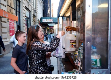 NEW YORK CITY - SEPTEMBER 25, 2016: Halal street food vendor on the corner of Broadway and Astor handing out food to a family of three