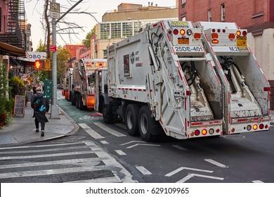 NEW YORK CITY - SEPTEMBER 25, 2016: Three white garbage trucks parked in line on 10th west street in Greenwich Village