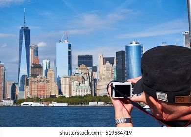 NEW YORK CITY - SEPTEMBER 26, 2016: Tourist leaning out from the Staten Island ferry to take a picture of Manhattan downtown skyline