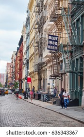 NEW YORK CITY - SEPTEMBER 28, 2016: Local life in Green Street with relaxed people next to the cobblestone paved street