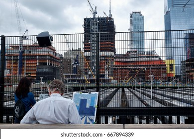 NEW YORK CITY - SEPTEMBER 28, 2016: Man sitting on High Line doing a painting of the Hudson Yards building