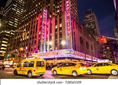 NEW YORK CITY - SEPTEMBER 28, 2017:  View of Radio City Music Hall in Manhattan seen at night with lights, cars, taxi's and Harry Styles on marquee.