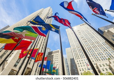 NEW YORK CITY - SEPTEMBER 3, 2016: Colorful flags fly in the breeze at the base of the Art Deco skyscrapers of Rockefeller Center.