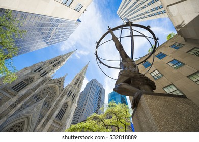 NEW YORK CITY - SEPTEMBER 3, 2016: The statue of Atlas in Rockefeller Center stands across from St Patrick's Cathedral on a bright summer morning.