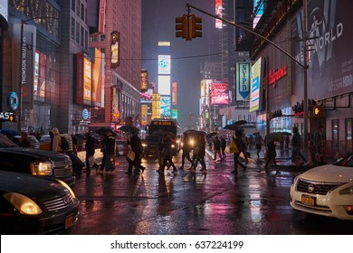 NEW YORK CITY - SEPTEMBER 30, 2016: Pedestrians with umbrellas crossing 7th Avenue between cars on a rainy evening