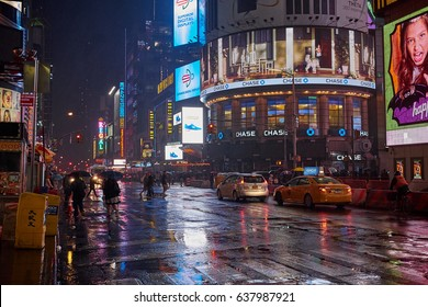 NEW YORK CITY - SEPTEMBER 30, 2016: People walking in the rain at night time on 42nd street near Times Square