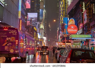 NEW YORK CITY - SEPTEMBER 30, 2016: Man walking on a rain wet 42nd Street between cars and busses at night time