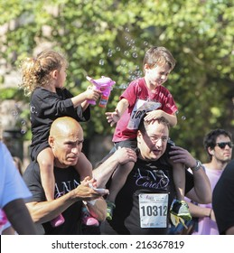 NEW YORK CITY - SEPTEMBER 7 2014: the Susan G Komen Race for the Cure took place along Central Park West with participants raising funds for breast cancer. Kids play bubbles on their dads' shoulders