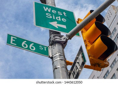 New york city signs and street light post east 66 street arrow pointing to west side one way sign