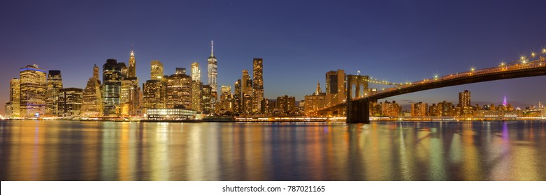 The New York City skyline and the Brooklyn Bridge photographed at night.