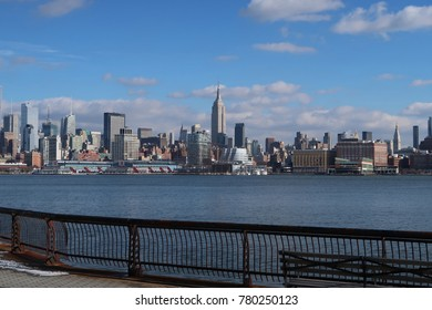 New York City skyline, from New Jersey, on a beautiful day. White puffy clouds in sky. Railing along bottom of image.