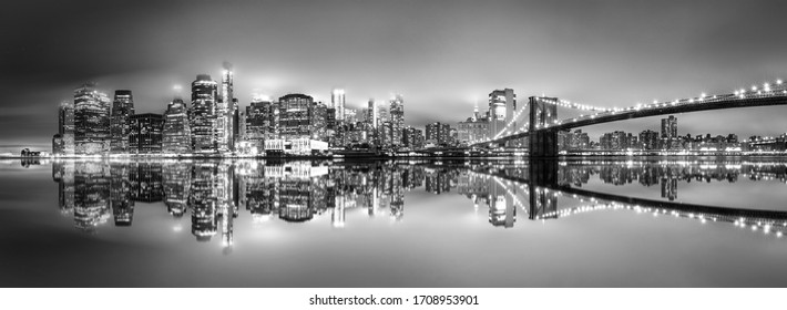 .New York City skyline with skyscrapers at sunset on Brooklyn Bridge black and white version.