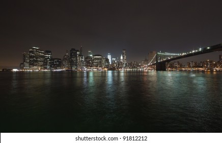 The New York City skyline at twilight w the Freedom tower and Brooklyn bridge