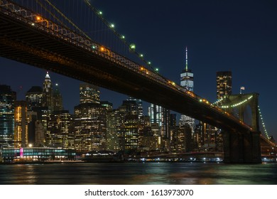 New York City Skyline under the Brooklyn Bridge at dusk.  View of the city scene at night viewed from DUMBO neighborhood.