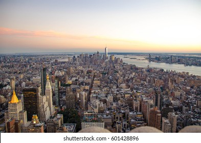 New York City skyline with urban skyscrapers at sunset. Architecture of the modern city. Aerial view of Manhattan island with soft lights and beautiful summer sky. The cultural and financial capital