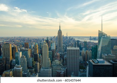New York City skyline with urban skyscrapers at sunset. The architecture of modern city. Aerial view of Manhattan island with a soft lights and beautiful summer sky. The cultural and financial capital