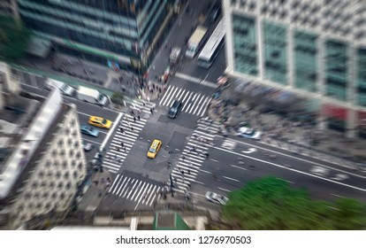 New York city street full of taxis, cars and pedestrians. Yellow cab in focus. Busy NYC Downtown. Crowd of people crossing crosswalks. Traffic jam in NY. Zoom blur effect.