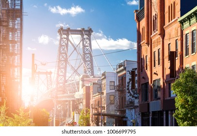 New York City street scene with sunlight shining on the Williamsburg Bridge in Brooklyn NYC