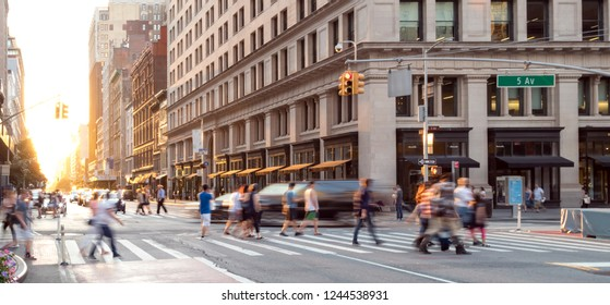New York City street scene with crowds of people walking through the busy intersection of 23rd and 5th Avenue in Midtown Manhattan