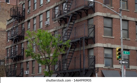 New York City style apartment building day time exterior establishing shot of rented living space above store front with fire escape along facade