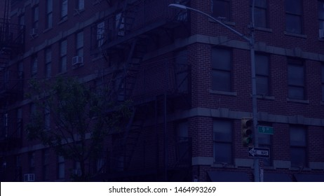 New York City style apartment building night time exterior establishing shot of rented living space above store front with fire escape along facade