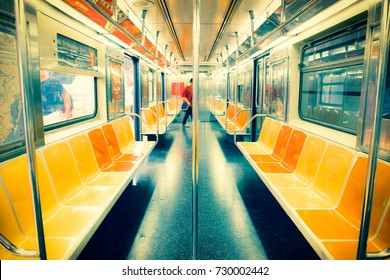 New York City subway car interior with colorful seats with passenger in the background