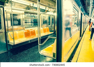 New York City subway car interior with colorful seats and commuters standing on station platform